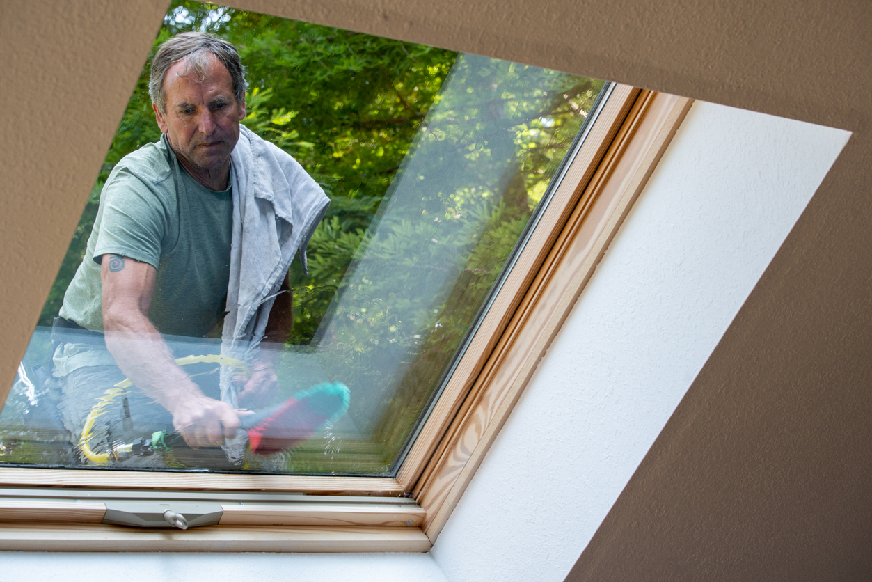 Man washing skylight on roof of house in California